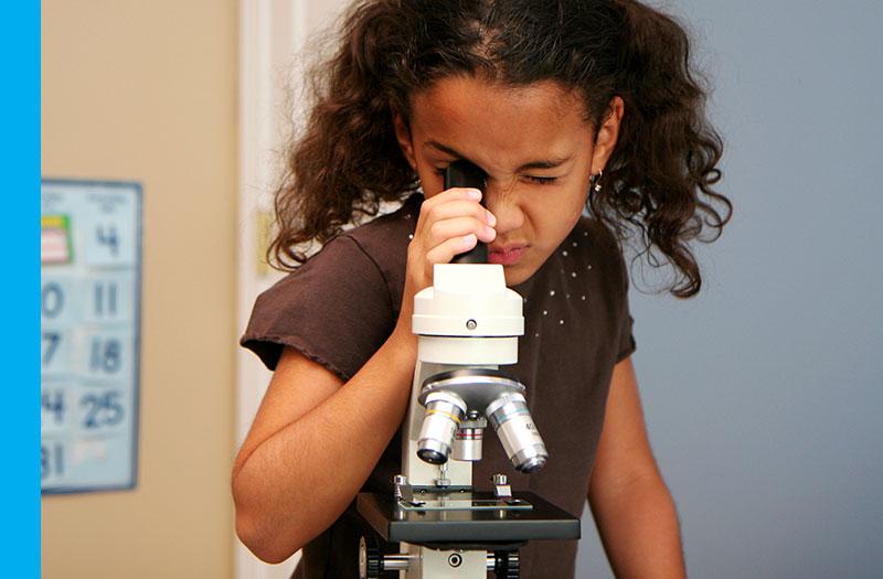 Young girl using microscope
