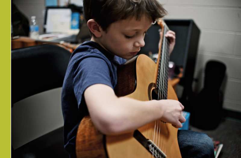 Young boy playing guitar at the Flint Institute of Music